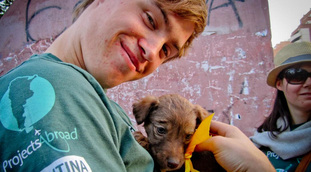 Animal care volunteer in Argentina takes a puppy to a community day to help find a new home for it.